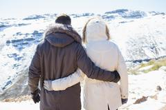 Couple in jackets looking at snowed mountain range - stock photo