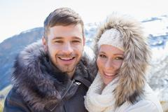 Loving couple in jackets against snowed mountain Stock Photos