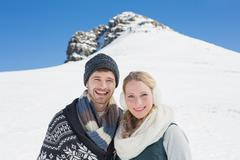 Couple in front of snowed hill and clear blue sky - stock photo