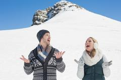 Couple with hands open standing in front of snowed hill Stock Photos