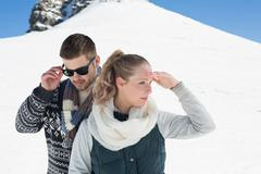 Couple in warm clothing against snowed hill - stock photo