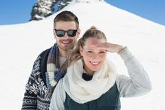 Happy couple in warm clothing in front of snowed hill Stock Photos