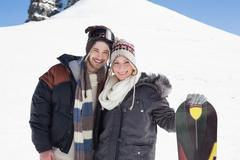 Portrait of a smiling couple in jackets with ski board - stock photo