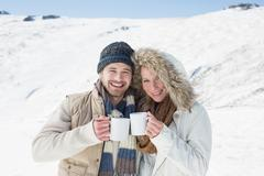Cheerful couple in warm clothing with coffee cups on snowed landscape - stock photo