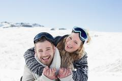 Stock Photo of Cheerful couple with ski goggles on snow