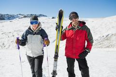 Stock Photo of Portrait of a smiling couple with ski equipment on snow
