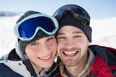 Stock Photo of Close up of a cheerful couple with ski goggles on snow
