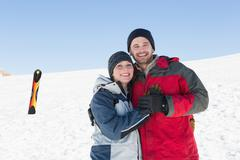 Happy loving couple with ski board on snow in background Stock Photos