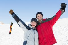 Couple raising hands with ski board on snow in background - stock photo