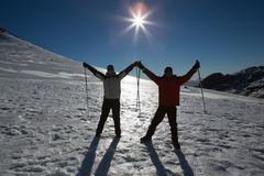 Silhouette couple raising hands with ski poles on snow - stock photo