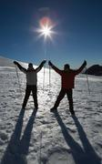 Silhouette couple raising hands with ski poles on snow Stock Photos