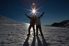 Silhouette couple with hands raised on snow against sun and blue sky - stock photo