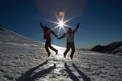 Silhouette couple jumping on snow against sun and blue sky - stock photo