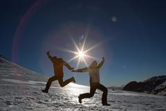 Silhouette couple jumping on snow against sun and blue sky Stock Photos