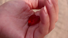 Red crystal heart in sea and surf. - stock footage