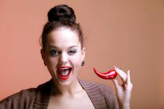 Beautiful woman with red lips and chilli pepper Stock Photos