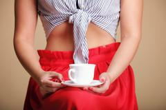 woman holding tea or coffee cup - stock photo