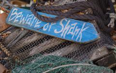 Beware of sharks wooden sign Stock Photos