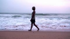 The girl is walking on the shore with a big surf waves. - stock footage