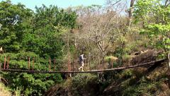 Guy crosses a ravine in the jungle on the rope footbridge. Stock Footage