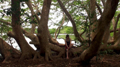 Guy resting on a bent tree by the lake in the Wilpattu NP. - stock footage