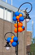 colourful balloons adorn the column with lantern on a city stree - stock photo