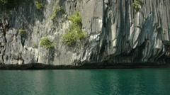 Drifting past limestone cliffs rising from calm, clear waters. - stock footage