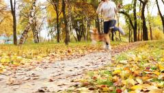 Girl  runs with beagle puppy in autumnal park Stock Footage