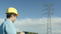 Electrical engineer in front of a power line. Stock Footage