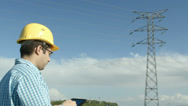 Stock Video Footage of Electrical engineer in front of a power line.