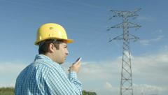 Electrical engineer in front of a power line. - stock footage