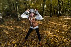crazy young woman makes fun in the autumn forest - stock photo