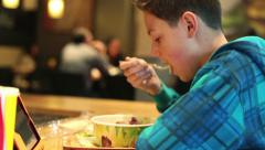 Young boy eating salad in fast food restaurant HD Stock Footage
