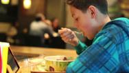 Stock Video Footage of Young boy eating salad in fast food restaurant HD