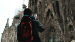 Boy taking picture of the cathedral Sagrada Familia on his smartphone HD Stock Footage