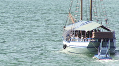Boat filled with people sails along waters Stock Footage