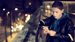 Young boy texting on smartphone in the city, in the night HD - stock footage