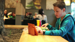 Boy using tablet computer and eating chips in fast food restaurant HD Stock Footage