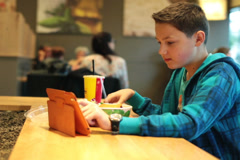 Boy using tablet computer and eating chips in fast food restaurant NTSC Stock Footage