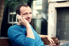 Young man talking on his cellphone sitting on bench in city NTSC Stock Footage