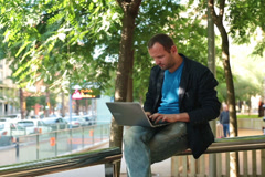 Happy young man finishing work on laptop sitting on handrail NTSC Stock Footage