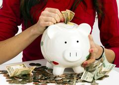 Woman stuffing us currency coins piggy bank cash savings Stock Photos