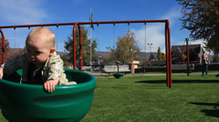Baby boy Spinning at the park playgroung. Stock Footage