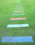 Wooden piece color path walk on green field. Stock Photos