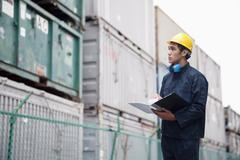 Young worker in protective work wear examining cargo in a shipping yard Stock Photos