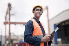 Proud young worker in protective work wear in a shipping yard - stock photo