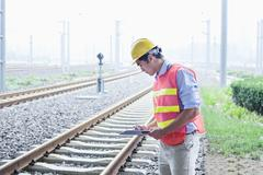 Railroad worker in protective work wear checking the railroad tracks - stock photo