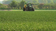 Farmer spraying pesticides on a field of wheat Stock Footage