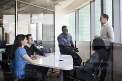 Five business people sitting at a conference table and discussing during a - stock photo