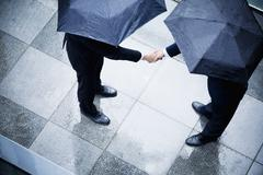 High angle view of two businessmen holding umbrellas and shaking hands in the - stock photo
